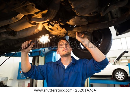Mechanic shining torch under car at the repair garage - stock photo