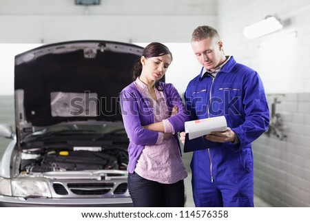 Mechanic showing a clipboard to a client in a garage