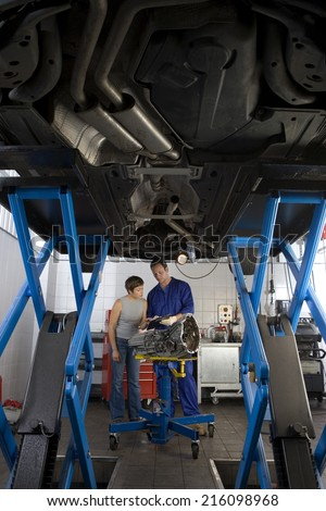 Mechanic showing clipboard to woman by elevated car, low angle view - stock photo