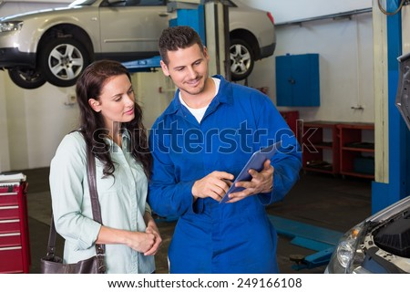 Mechanic showing tablet pc to customer at the repair garage - stock photo