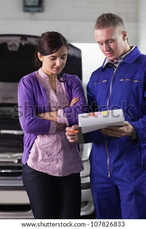 Mechanic showing the quotation to a woman in a garage