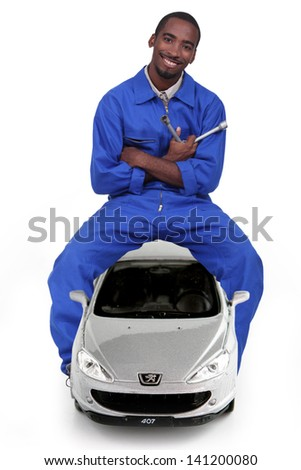 Mechanic sitting on a car and holding a lug wrench - stock photo