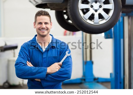 Mechanic smiling at the camera holding tool at the repair garage - stock photo