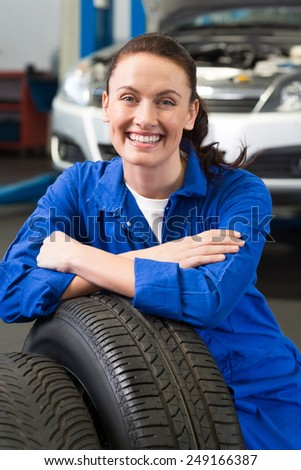 Mechanic smiling at the camera with tire at the repair garage