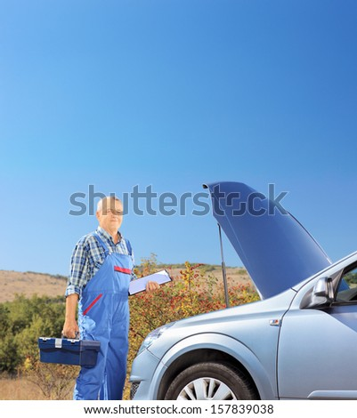 Mechanic standing near a broken car with open hood, on a road, shot with a tilt and shift lens - stock photo