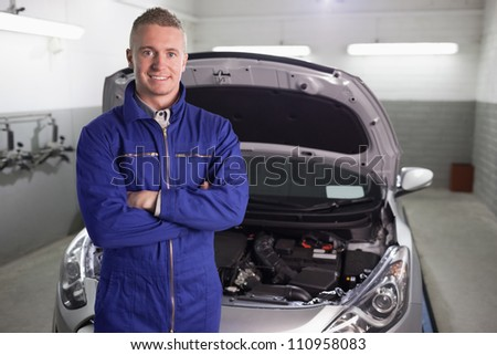 Mechanic standing with arms crossed in a garage