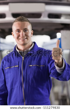 Mechanic standing with thumb up next to a car in a garage