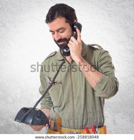 mechanic talking to vintage phone  - stock photo