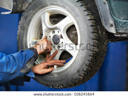 mechanic technician worker installing car wheel at maintenance and repair auto service station - stock photo