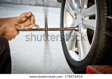 Mechanic technician worker replacing damaged wheel drive vehicle - stock photo