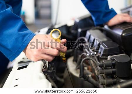 Mechanic testing oil in car at the repair garage - stock photo