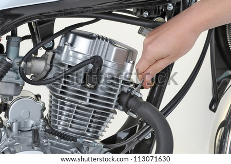 mechanic tightening the exhaust on a motorcycle engine - stock photo