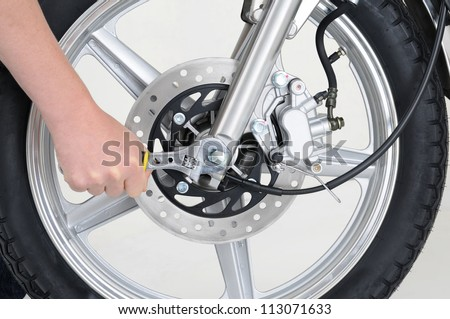 mechanic tightening the wheel nut on a motorcycle