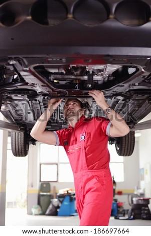 mechanic under the car - stock photo