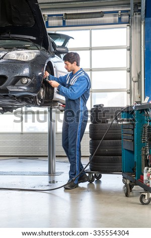 Mechanic, using a calipher, to check the thickness of a brake disk of a vehicle on a car lift. A stack of tires and a tools trolley behind him - stock photo