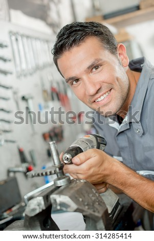 Mechanic using a drill to adjust part