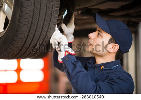 Mechanic using a lamp to inspect a lifted car - stock photo