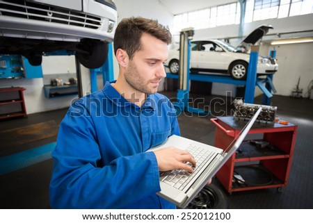 Mechanic using a laptop to work at the repair garage