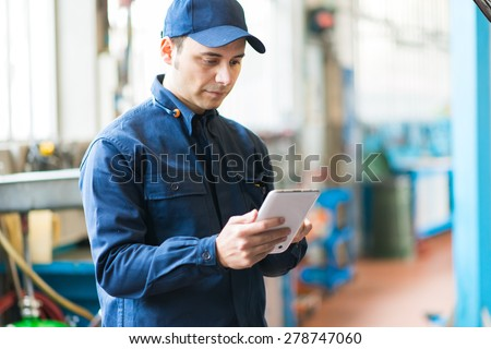 Mechanic using a tablet in his garage - stock photo