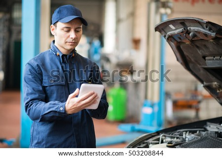 Mechanic using a tablet in his shop