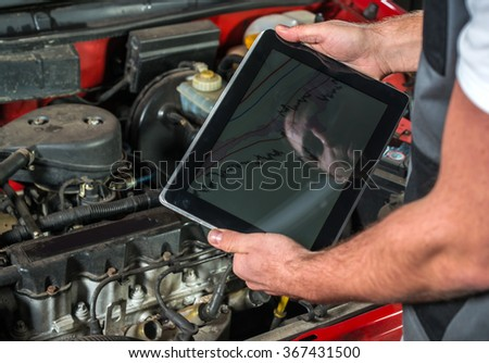 Mechanic using a tablet pc at the repair garage - stock photo