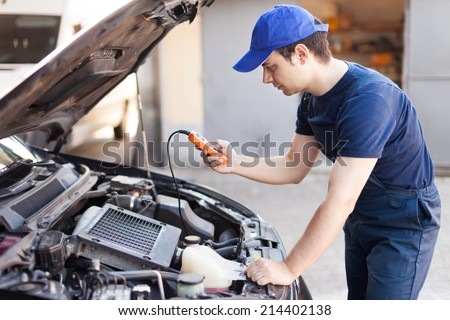 Mechanic using an electronic tester on a car engine - stock photo