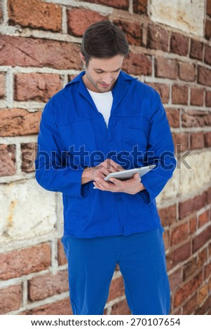 Mechanic using digital tablet over white background against red brick wall - stock photo