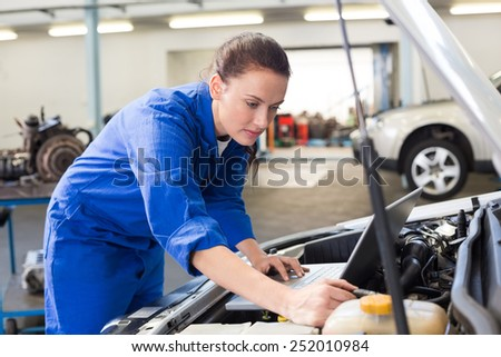 Mechanic using laptop on car at the repair garage