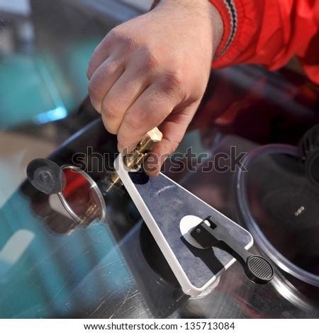 Mechanic using repairing equipment to fix damaged windshield - stock photo