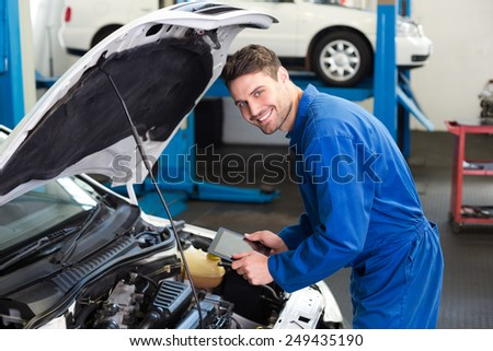 Mechanic using tablet to fix car at the repair garage - stock photo