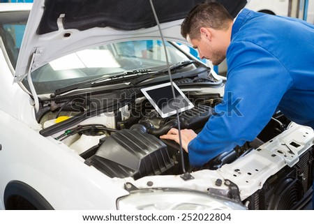 Mechanic using tablet to fix car at the repair garage