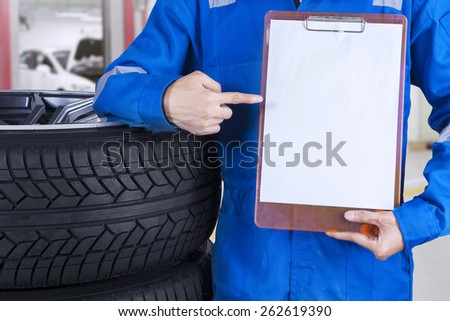 Mechanic with a blue work wear showing an empty copyspace while standing next to tires - stock photo