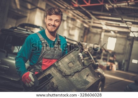 Mechanic with car bumper in a workshop - stock photo