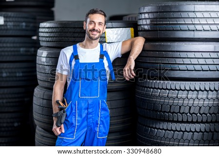 mechanic with car tires in tire store - stock photo