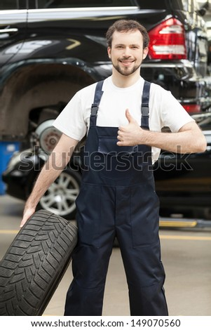 Mechanic with car wheel. Cheerful young auto mechanic holding a car wheel and smiling - stock photo