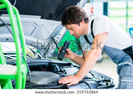 Mechanic with diagnostic tool in car workshop - stock photo