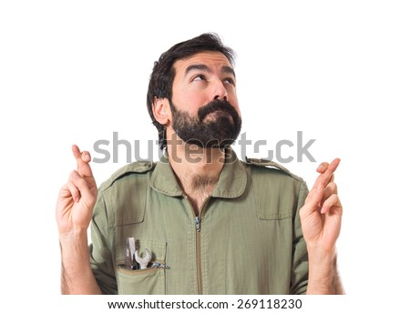 Mechanic with his fingers crossing   - stock photo