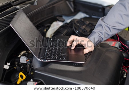 Mechanic with laptop diagnoses car in workshop. - stock photo