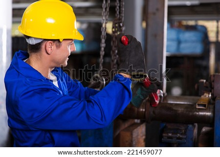 mechanic with monkey wrench repairing factory pipes