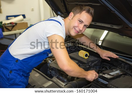 Mechanic with tools in garage or workshop repairing the motor of a car