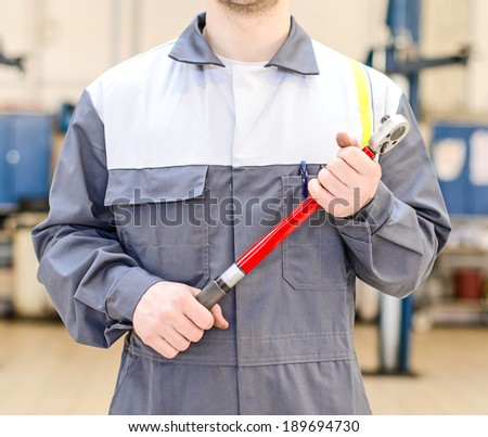 Mechanic with torque wrench at auto repair shop. - stock photo
