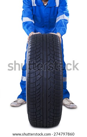 Mechanic with uniform pushing a black tire to change another tire, isolated on white - stock photo