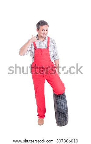 Mechanic with wheel tire making call me gesture as contact person concept