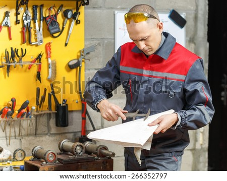 Mechanic worker studying his instructions at a construction home studio