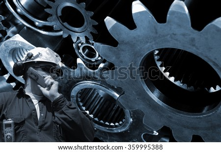 mechanic, worker with large cogwheels machinery in background - stock photo