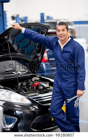 Mechanic working at the garage and fixing a car