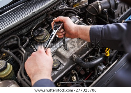 Mechanic working in a car under the hood, repairing an engine