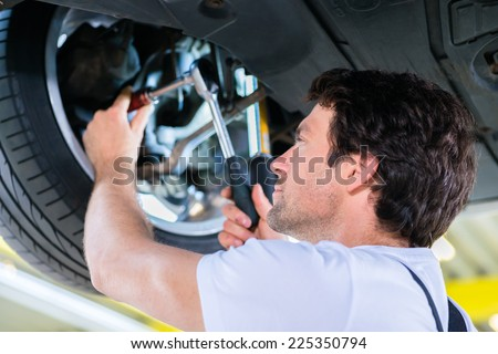 Mechanic working in car workshop on wheel - stock photo