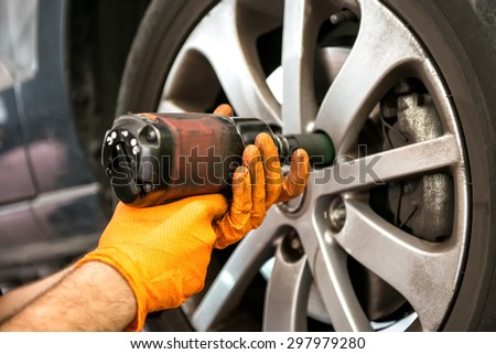 Mechanic working on a car wheel tightening or loosening the bolts on the hub and rim with an electric power tool, close up view of his hands