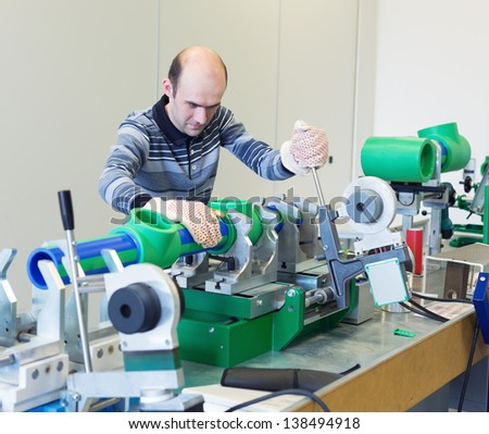 Mechanic working on a machine at workroom - stock photo